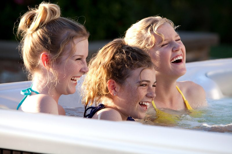 A hot tub like the Hot Springs Highlife® Aria promotes bonding among siblings and friends.